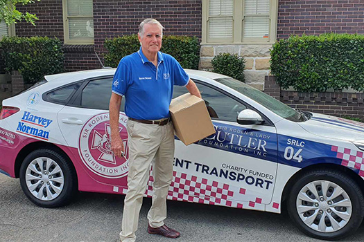 Man in front of car holding a box
