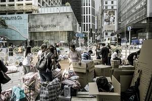 domestic helper dismantling cardboard in streets of Hong Kong