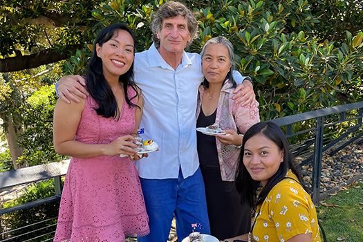 Three females standing with a man, eating cake