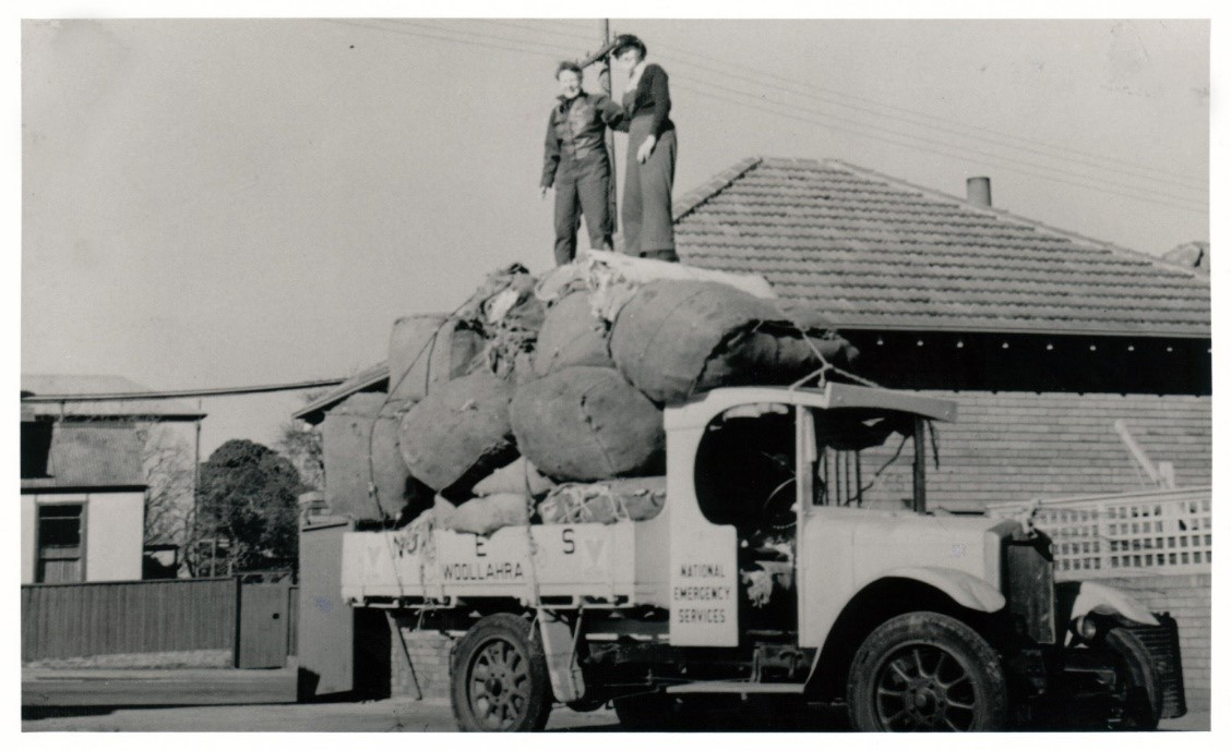 Volunteers with the Woollahra branch of the National Emergency Services distribute sand bags from the top of a vehicle. <em>Woollahra Libraries Digital Archive pf002977</em>.
