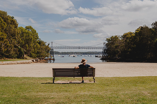 Man sitting on park bench overlooking the water and Parsley Bay suspension bridge