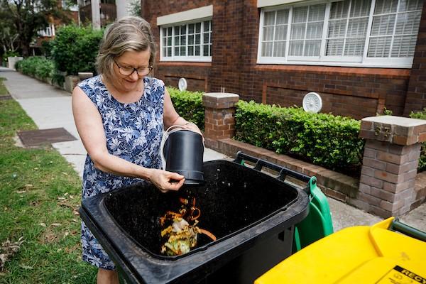 Female placing compost into bin