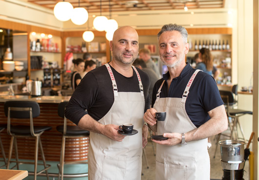 Two baristas at Barbetta holding coffee cups