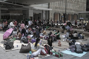 Domestic helpers in Hong Kong sitting on boxes