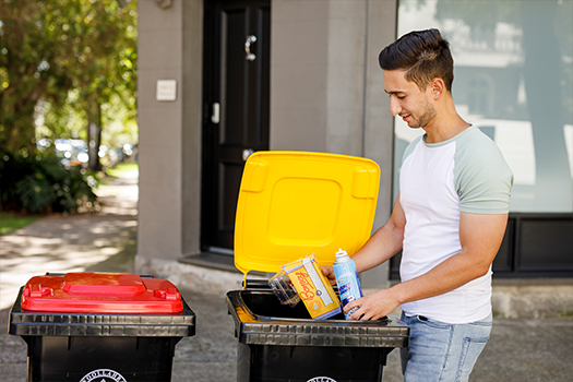 Man putting items into yellow lid recycling bin