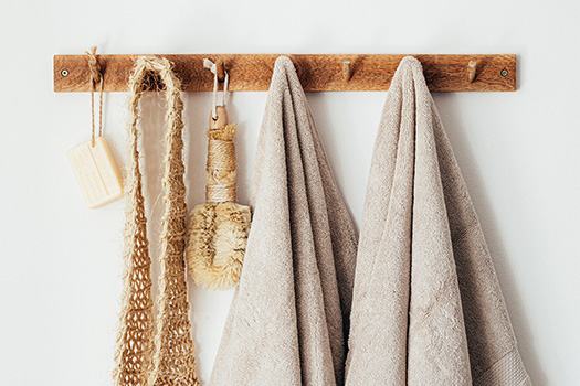Plastic free bathroom products and towels hanging on a wooden rack