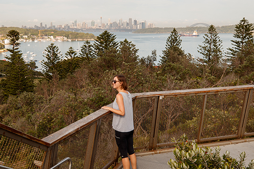 Woman standing in Gap Park looking at city and harbour skyline