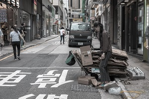 Woman collects cardboard boxes in Street