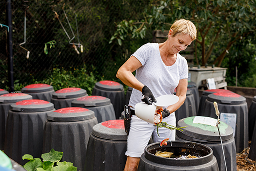 Woman putting food scraps into compost bin