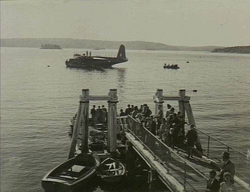 Elevated view of a group of civilians on the wharf at the flying boat base at Rose Bay, waiting to be ferried out to the Short Sunderland aircraft (in background) for a joy-flight. The aircraft, now captained by Flight Lieutenant (Flt Lt) Manger who had replaced Flt Lt M. S. Mainprize DFC, was making a tour of Australian states in support of the 3rd Victory Loan and, during each stop on the tour, took eligible subscribers of 100 pounds or more to the loan for a joy-flight. AWM VIC1263 31 May 1945