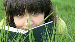 girl reading on grass