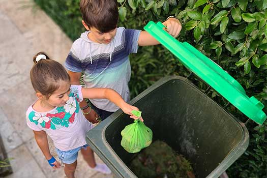 Two kids putting a green compostable bag into a green bin