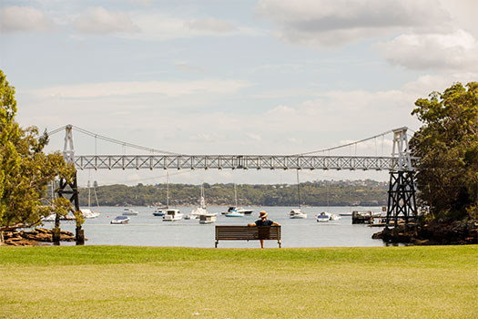 Man sitting on park bench looking at the Parsley Bay Bridge