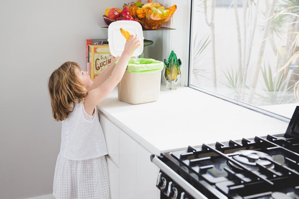 Girl putting food scraps into caddy bin