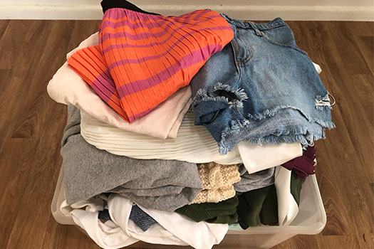 A pile of clothes sitting inside a plastic tub