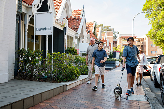 Family with dog walking along  Transvaal Avenue with shops behind them